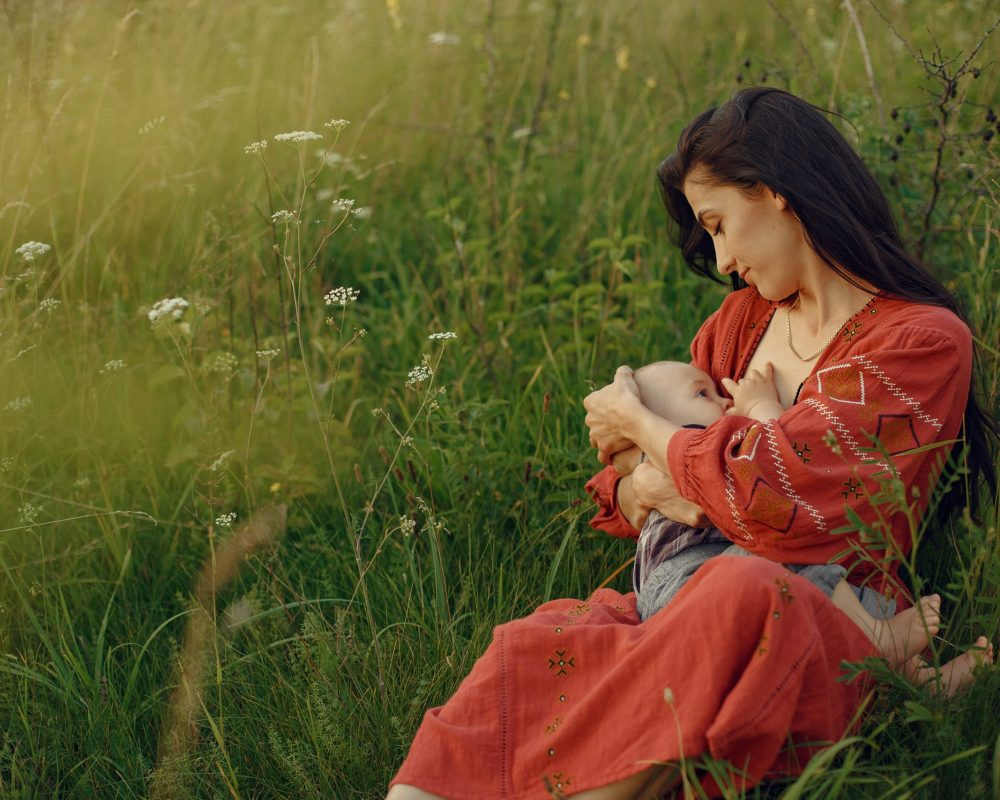 Mother with cute daughter. Mom breastfeeding her little son. Woman in a red dress.